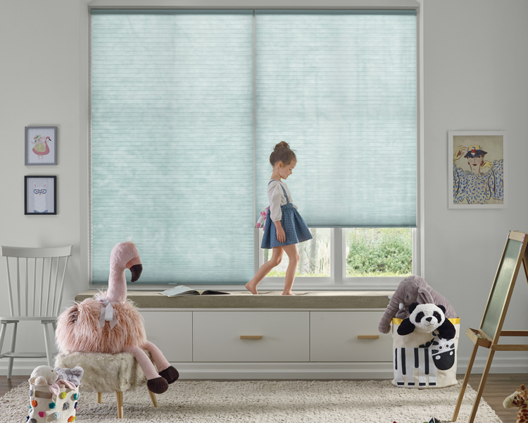 girl standing on window seal with blue honeycomb shades by Hunter Douglas Reno