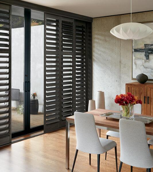 modern dining room with sliding glass doors and Hunter Douglas black plantation shutters Reno 89439