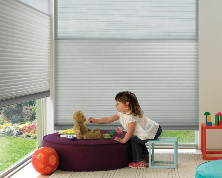 girl playing with teddy bear in playroom with red ball and Hunter Douglas child safe cordless blinds duette honeycomb shades Reno
