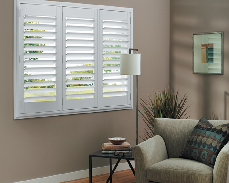 green chair in neutral living room with plantation shutters child-safe blinds by hunter douglas Remp 89520