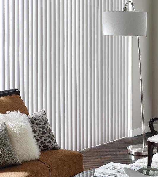 modern living room with brown velvet sofa and cadence soft vertical blinds on sliding glass door by Hunter Douglas Reno