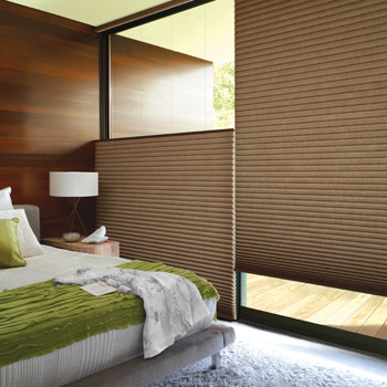 master bedroom with green bedding and hunter douglas honeycomb shades with top down bottom up shades window covering solutions Reno