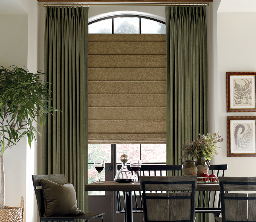 dining room with layered window treatments of draperies and roman shades on gold hardware Reno NV