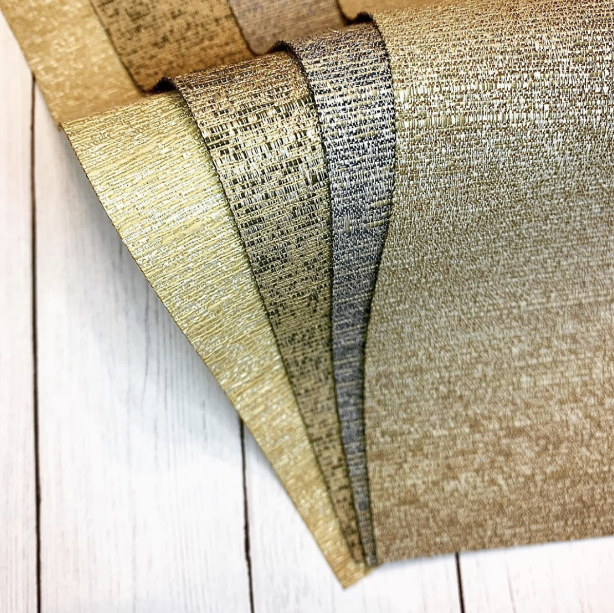 Metallic gold fabric swatches for window treatments.