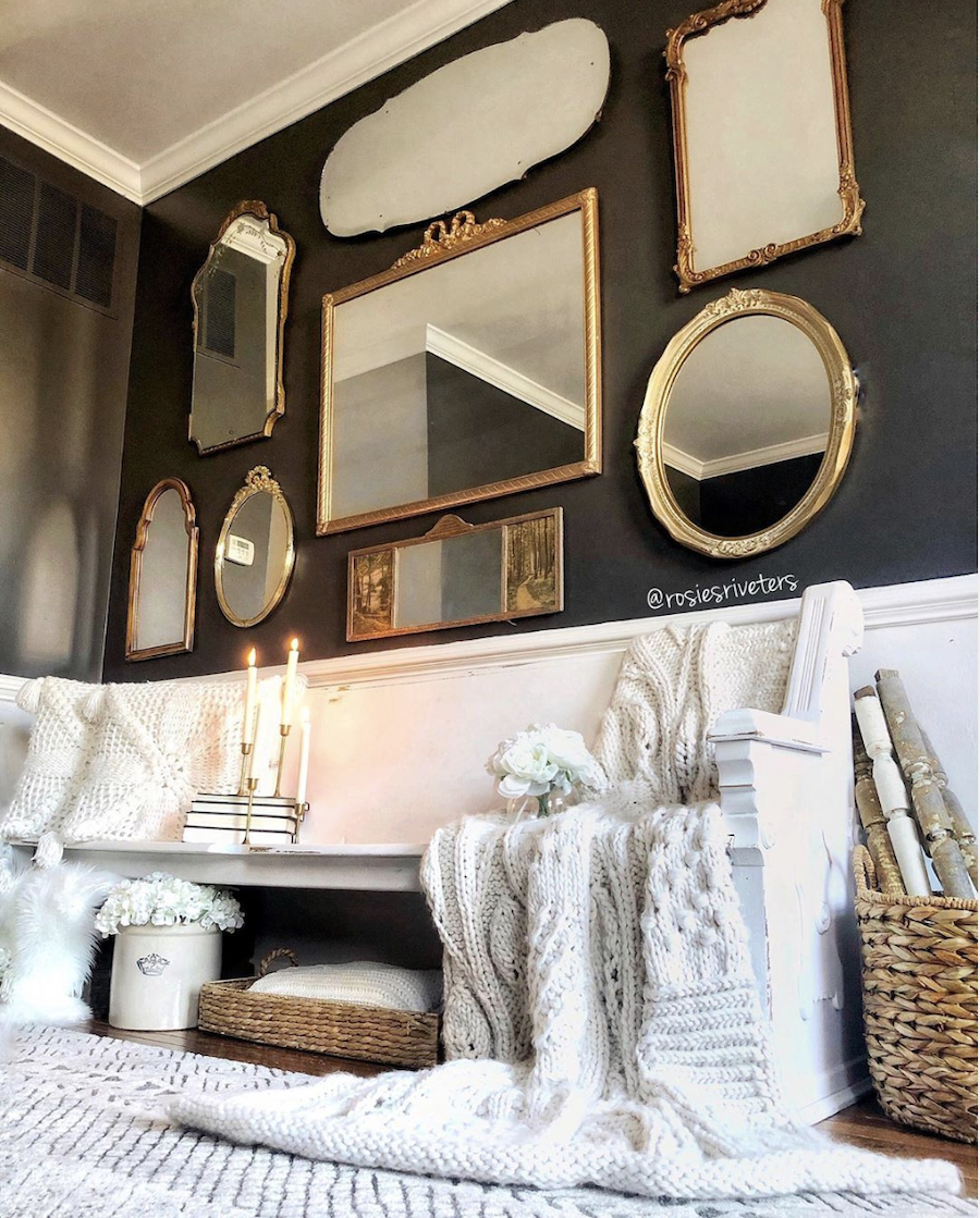 Gold, vintage mirrors on a dark accent wall.