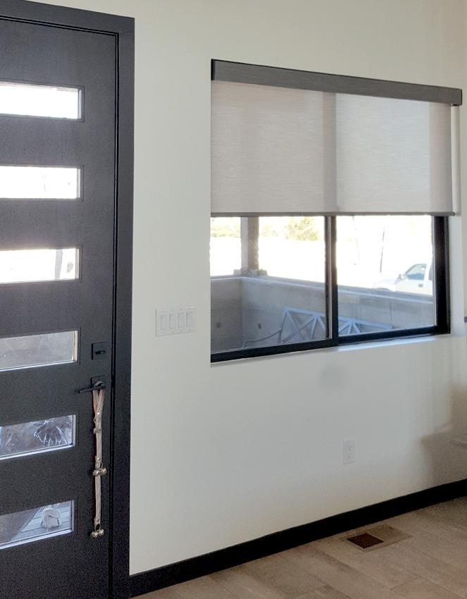 entryway window with neutral color roller shades by door in Reno NV home
