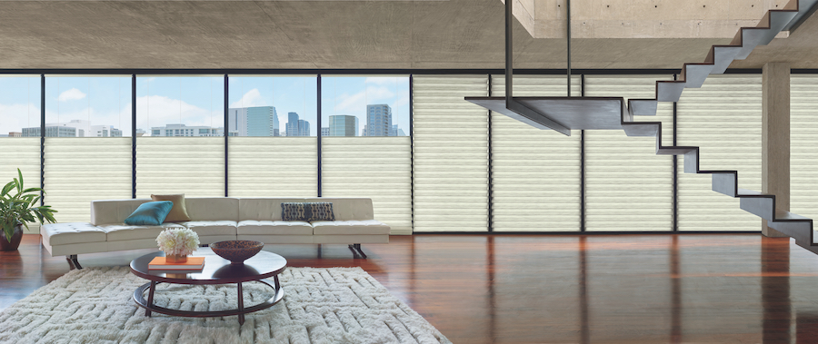 A loft with wall to wall windows with automated shades.