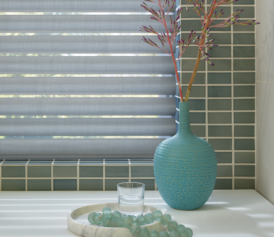 green subway tile bathroom with gray window shades in Reno NV