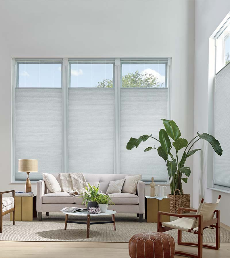 contemporary white living room with honeycomb shades on tall windows in Reno NV for window covering solutions