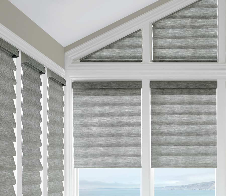 gray roman shades framed by white wood beams in corner window