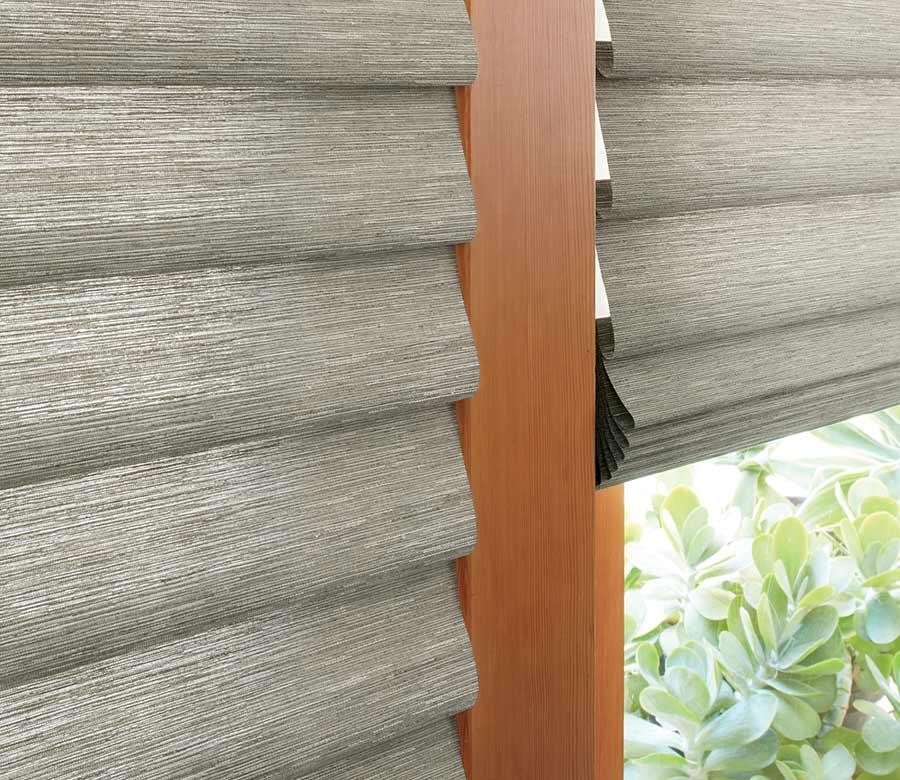 detail of gray roman shades on glass patio door