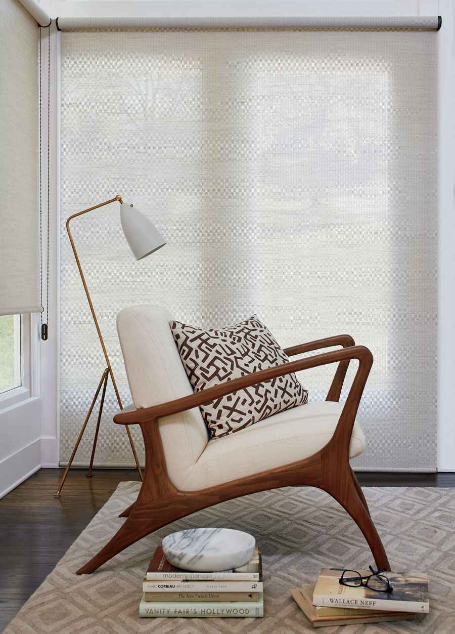 floor to ceiling cream shades next to mid-century modern chair